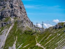 Three high voltage post power poles high up in the mountains high voltage tower switzerland alps. Sunny stock photos