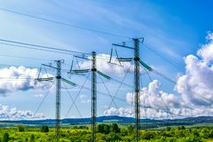 Three high voltage transmission towers over cloudy sky Royalty Free Stock Photos