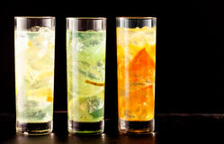 Three highball glasses filled with cocktail drinks. Three highball glasses filled with alcoholic or non-alcoholic cocktail drinks mixed with ice and tropical Stock Photos