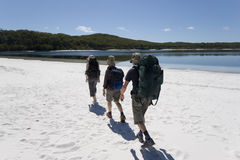 Three hikers in australia 2. Three hikers walking on a beach in australia on fraser island on a clear sunny day 1 Royalty Free Stock Photo