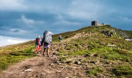 Three hikers walking in the mountains Royalty Free Stock Photography