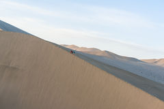 Three hikers climb on the sand dunes Stock Images