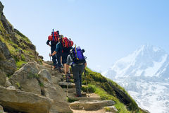 Three hikers in mountains Stock Photo