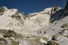 Three hikers in red clothes in winter Tatra mountains royalty free stock photos