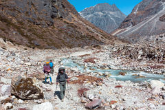 Three Hikers walking on rocky Footpath along wild Mountain River Royalty Free Stock Photography