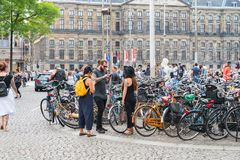 Three hip people standing next to bicycle park area using mobil. AMSTERDAM, HOLLAND - AUGUST 17, 2017; Three hip people standing next to bicycle park area using stock photos