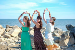 Three hippie girls show their hands a heart by the sea stock images