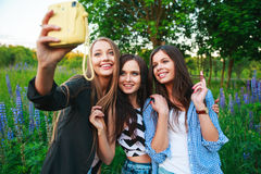 Three hipsters girls blonde and brunette taking self portrait on polaroid camera and smiling outdoor. Girls having fun together. In park Stock Photo