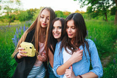 Three hipsters girls blonde and brunette taking self portrait on polaroid camera and smiling outdoor. Girls having fun together. In park Royalty Free Stock Photos