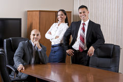 Three Hispanic office workers in boardroom Royalty Free Stock Photography