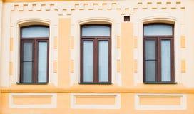 Three historic brown window on the yellow wall Stock Photos