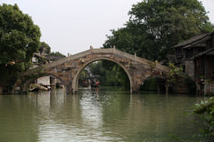 Three hole in the stone bridge. Houses on either side of the river, people on the steps washing Royalty Free Stock Image