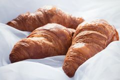 Three homemade croissants laying on white sheets Stock Photos