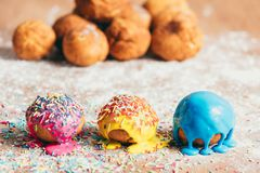 Three homemade doughnuts on a dirty counter. Three colorful homemade doughnuts on a dirty kitchen counter. Baking decorations Royalty Free Stock Photos