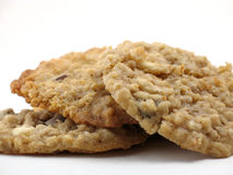 Three homemade oatmeal cookies. A small pile of three homemade oatmeal cookies, macro close-up on white Stock Image