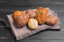 Three homemade rye buns. With grit poppy, sesame and flax seeds, three rye buns with pumpkin seeds, homemade bun made with white flour, burlap cloth, on dark Royalty Free Stock Photo