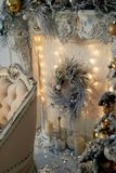 Three-horn candlestick, garland. White and silver decor. The new year atmosphere.Christmas decoration at home. Three-horn candlestick, garland. White and silver stock images