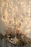 Three-horn candlestick, garland. White and silver decor. The new year atmosphere.Christmas decoration at home. Three-horn candlestick, garland. White and silver stock photo