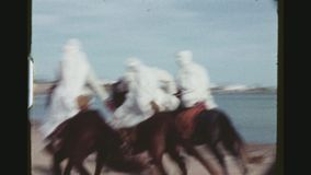 Three Horsemen Riding Fast. TUNISIA, GABES REGION, WINTER 1973. Two Shot Sequence With Pan Of Three Horsemen Riding In Preparation For The Yearly Sahara Folklore stock video footage
