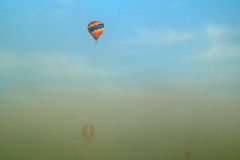 Three hot air balloons flying through morning fog Royalty Free Stock Image