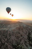 Three hot air baloons over a desert landscape at sunrise. Stock Photos