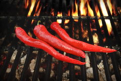 Three Hot Chili Peppers On The Flaming BBQ Grill Stock Photo