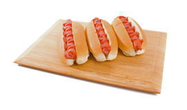 Three Hot Dogs on board isolated over white Stock Photography