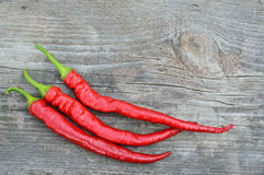 Three hot red peppers on the wooden board Stock Image