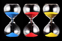 Three hourglasses with colorful sand Stock Image