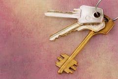 Three house keys on keyring over grunge background Royalty Free Stock Images