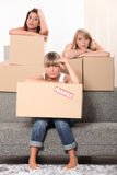 Three housemates with boxes Royalty Free Stock Photography
