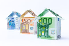 Three houses made of bank notes. Three houses made of different euro notes isolated on white background Stock Photos