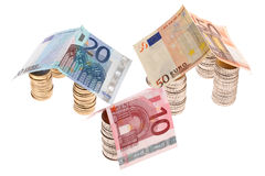 Three houses made of euro coins and paper money Royalty Free Stock Photography
