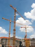 Three Huge Cranes on Construction Site in the Centre of a City Stock Images