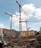 Three Huge Cranes on Construction Site in the Centre of a City Royalty Free Stock Image