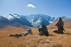Three hunters looking through binoculars in mountains of Tien Sh Stock Photography
