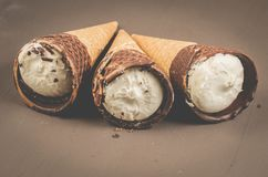 Three ice cream with cone in chocolate on a dark background/three ice cream with cone in chocolate, selective focus stock photos