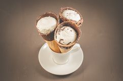 three ice cream with cone in chocolate on a in a white cup/three ice cream with cone in chocolate on a in a white cup, top view stock photography