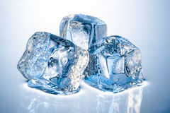 Three ice cubes. On blue background stock images