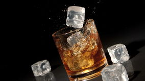 Three ice cubes falling into tumbler of whiskey and ice