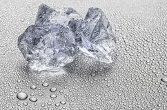 Three ice cubes on a metallic surface with water drops Royalty Free Stock Photography