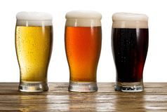 Three iced glasses of beer on the wooden table. stock image