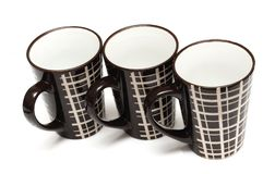 Three identical big tall dark brown coffee cups with simple lines design stock photo