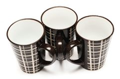 Three identical big tall dark brown coffee cups with simple lines design stock photography