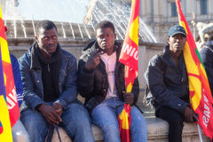 Three immigrants with flags. Rome, Italy - November 14, 2014: Protest of immigrants of color, gathered in square Esedra and then marching in the streets of the royalty free stock photography