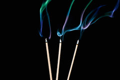 Three incense sticks with smoke on black background. Three incense sticks and smoke on black background Stock Photography
