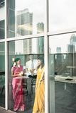 Indian employees sticking reminders on glass wall in the office. Three Indian employees sticking reminders on glass wall with business tasks and deadlines in the Stock Photo