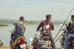 Three Indian guys on motorcycles on the ferry against the background of the river and the green stock photo