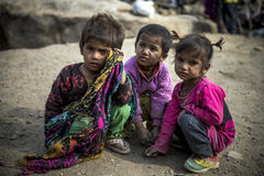 Three indian young kids group together squat on sandy street. Group of kids play on street while waiting for parents to finish work Royalty Free Stock Image