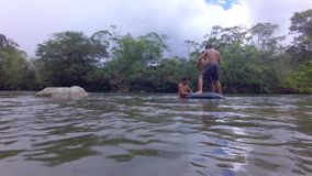 Three Indigenous Children Trying To Stand In A Floating Inner Tube. In Ecuador stock video footage